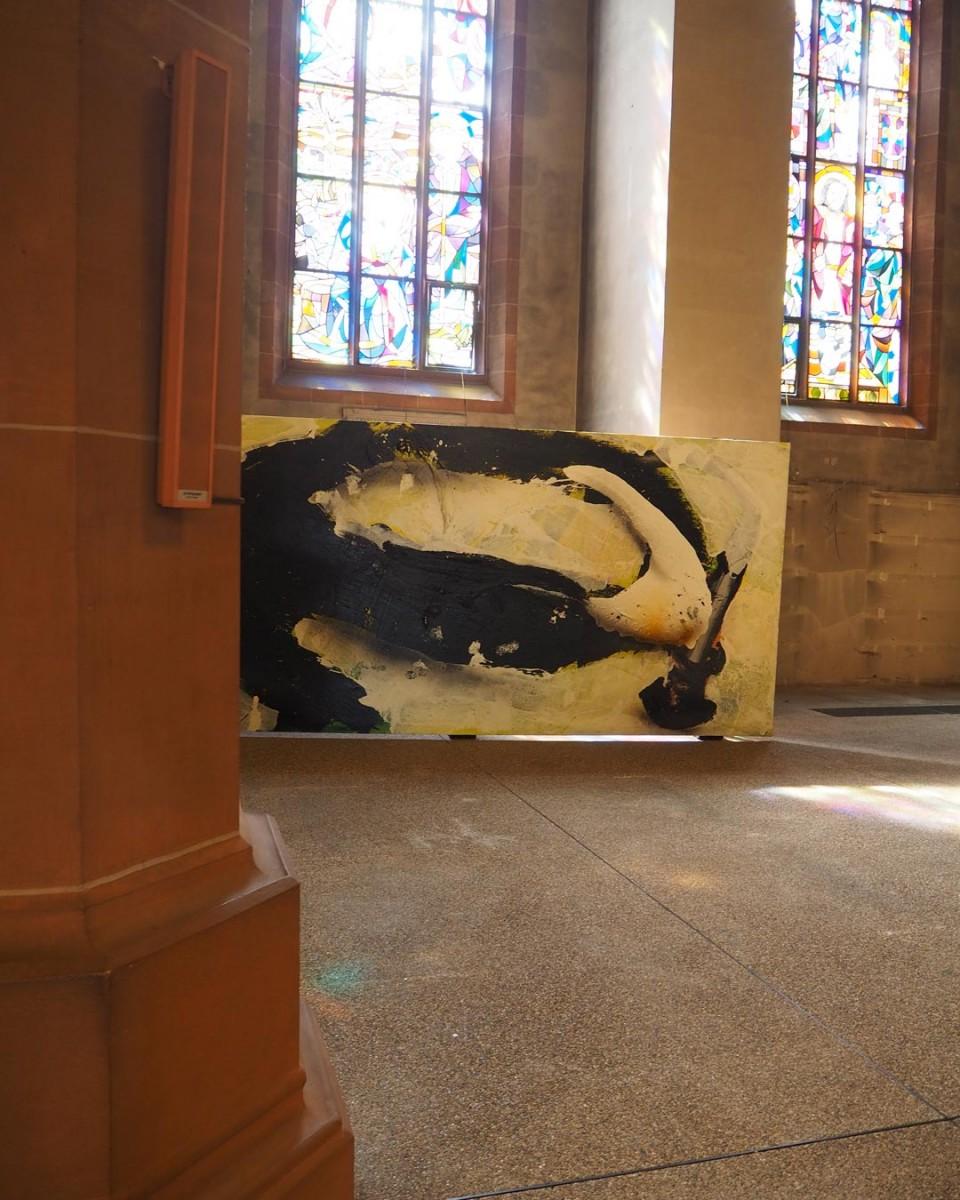 """Das """"E"""" von Dieter Kriegs Kunstwerk """"Fettquell"""" schaut hinter einer Kirchensäule hervor"""