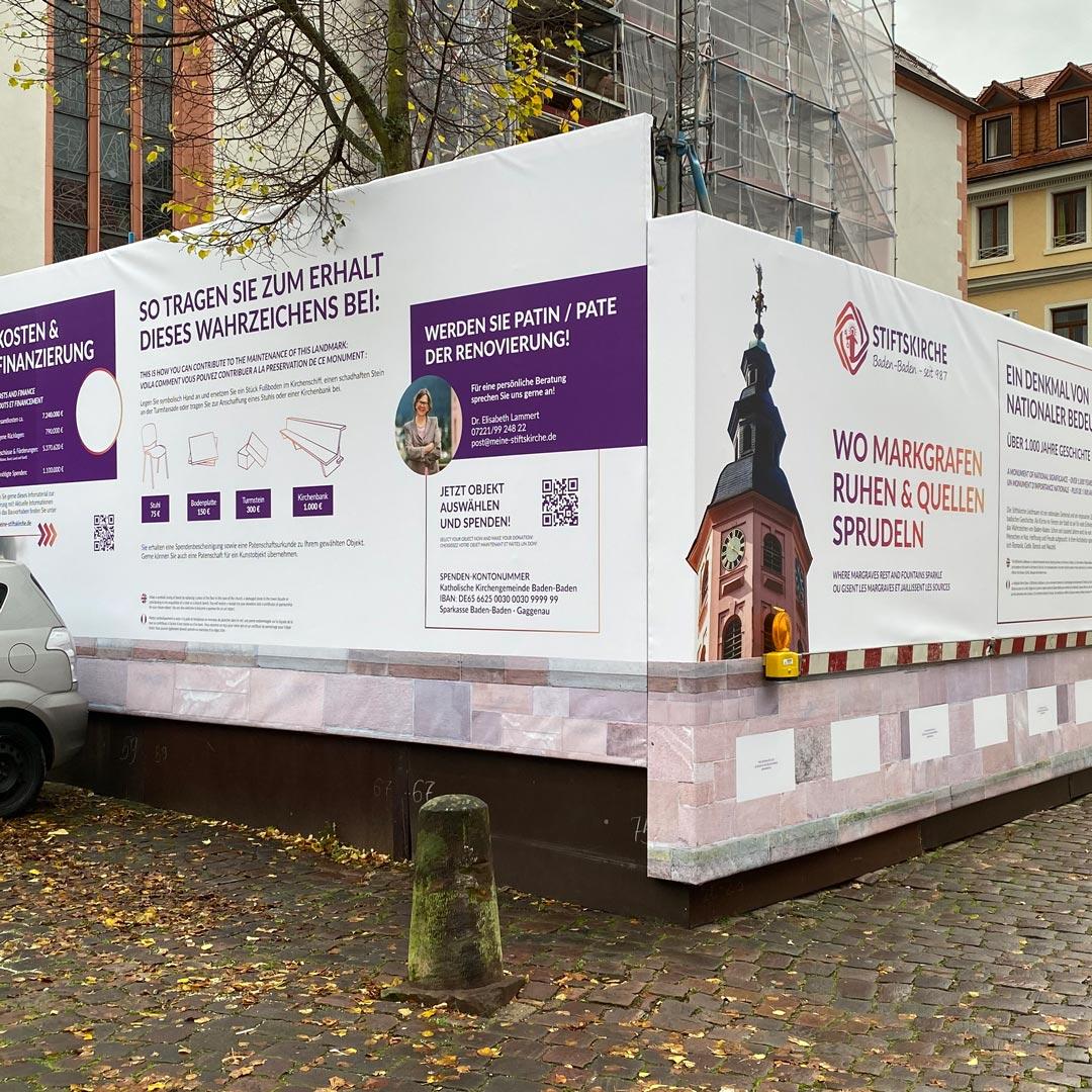 Der neue Bauzaunbanner macht auch auf die Spendenkampagne zugunsten der Renovierung aufmerksam